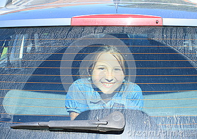 Girl watching from car trunk