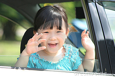 Girl waving goodbye in a car.
