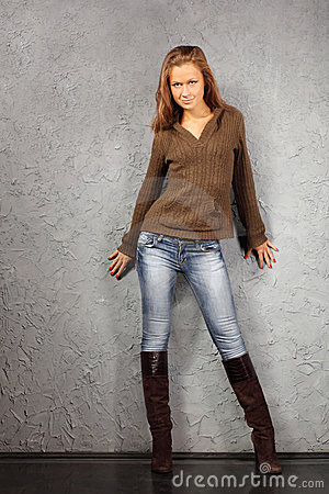 Girl wearing blouse and boots stand near wall