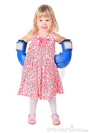 Girl wearing dress and boxers gloves is standing