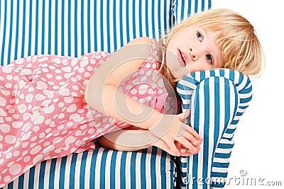 Girl wearing dress is lying on comfortable chair