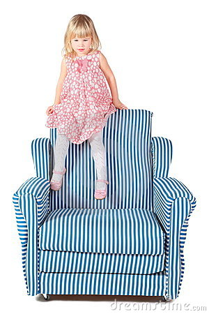 Girl wearing dress is sitting on back of chair