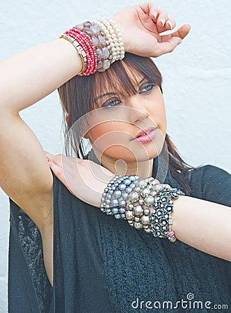 Girl wearing jewelry on both wrists. .