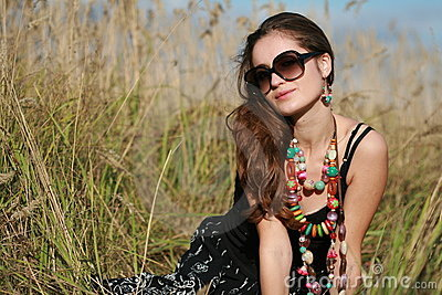 Girl wearing jewelry and sunglasses sits on field
