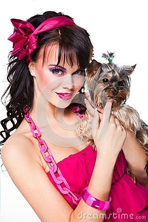 Girl wearing pink holding small dog on white