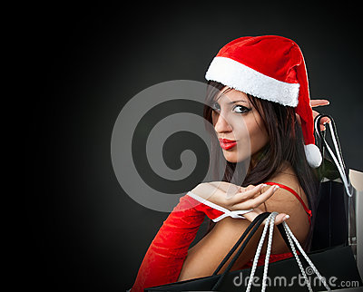 Girl wearing santa claus clothes with shopping ba