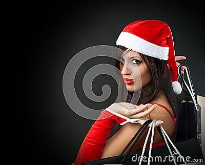Girl wearing santa claus clothes with shopping ba