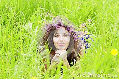 Girl wearing a wreath of wild flowers in the field