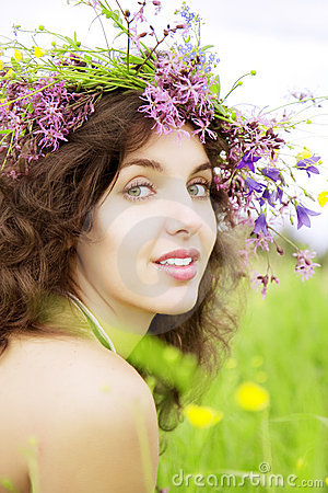 Girl wearing a wreath of wild flowers in the field