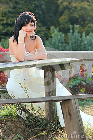 Girl in the wedding dress sitting on the bench