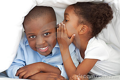 A girl whispering something to her brother