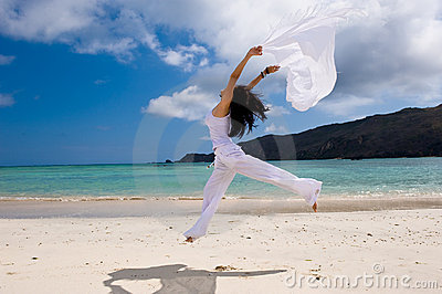 Girl with white cloth jumping on the beach
