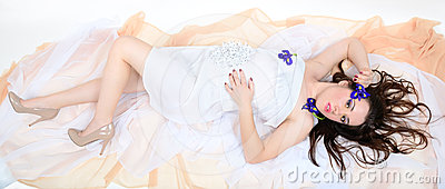 Girl in a white cloth lies on fabrics