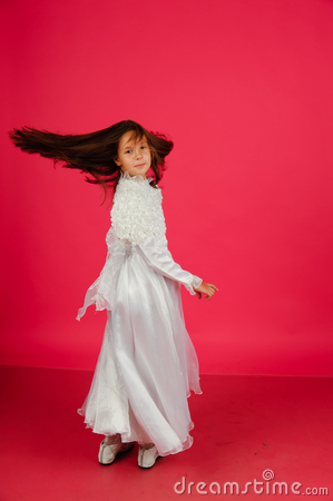 The girl in a white dress on a pink background