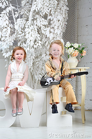 girl in white dress and pop musician with guitar sit