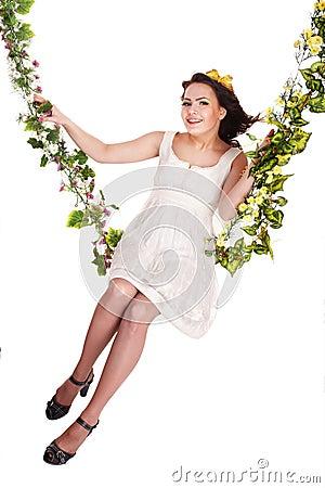 Girl in white dress swinging on flower swing.