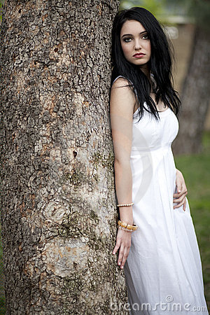 Girl in white dress by tree