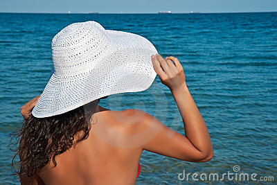 Girl in a white hat against the sea