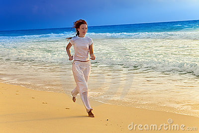 The girl in a white jumpsuit is engaged in fitness