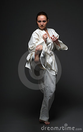 Girl in white kimono kicks forward right leg