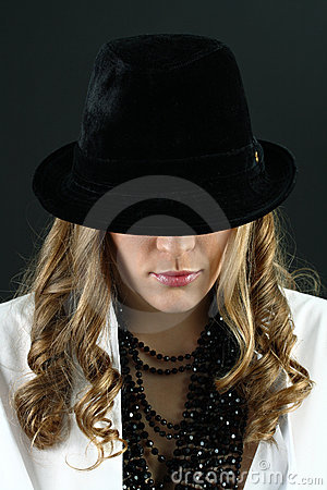 Girl in white shirt hiding  face under black hat