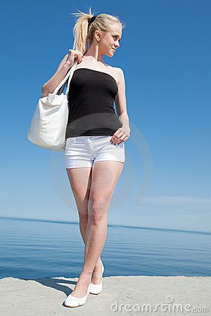 Girl in white shorts on background of the sea