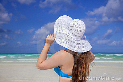 Girl with white sun hat sky and  carribean sea