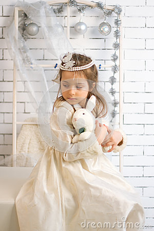 Girl in winter holiday dress with toy rabbit
