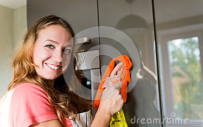 Girl wiping the dust from furniture at home