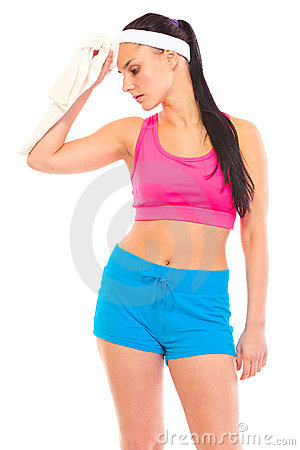 Girl wiping face with towel after exercising
