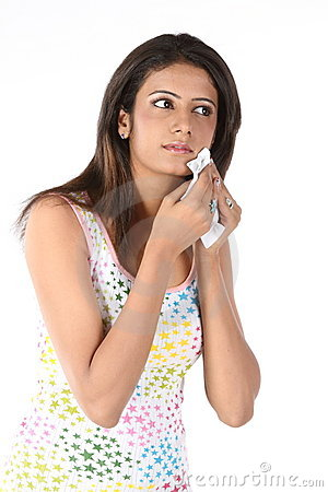 Girl wiping her face with tissue paper