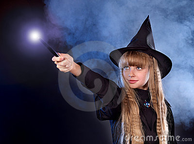 Girl in witch s hat with magic wand.