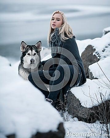 Free Girl With Dog Malamute Among Rocks In Winter. Stock Photo - 83762840