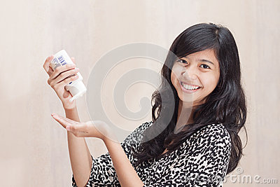Beautiful Asian girl using lotion for caring her skin