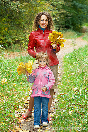 Girl and woman with maple leaves in park in autumn