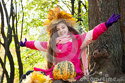 Girl in a wreath of maple leaves in park