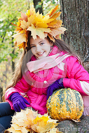 Girl in a wreath of maple leaves with pumpkin