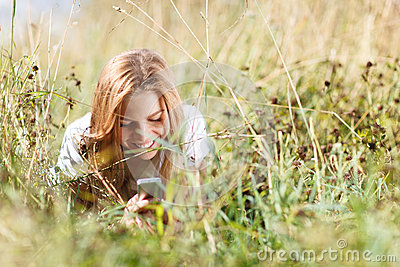 Girl is writing sms on the phone lying in grass