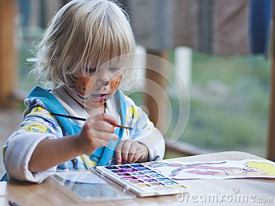 The girl of 3 years draws paints