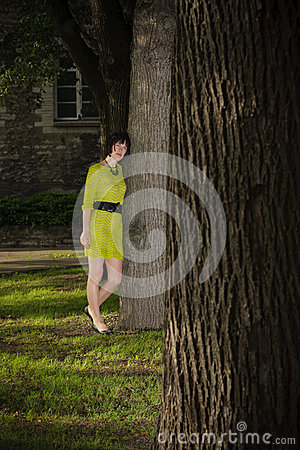 Girl in yellow dress leans on a tree in a park