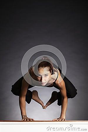 Girl in yoga crow pose.