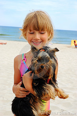 Girl with yorkshire dog on the beach