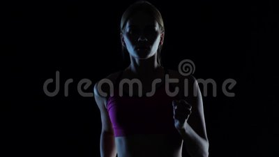 Girl young in pink top runs on a black background. Silhouette. Slow motion. Close up. Girl young in sporty pink top runs on a black background. Silhouette. Slow stock video footage