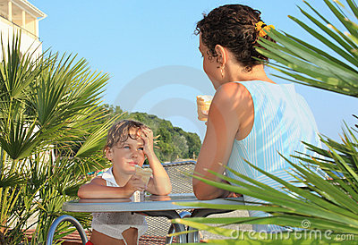 Girl and young woman eat ice-cream near palm trees