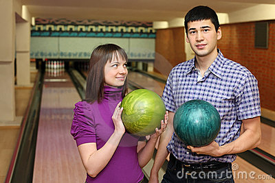 Girl and youth stand with balls for bowling