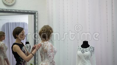 Girlfriends chooses wedding gown at boutique.  stock video footage