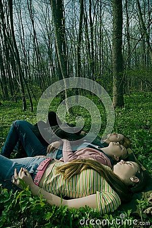 Girlfriends relaxing in forest