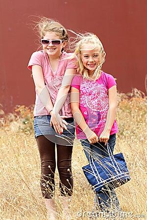 Girlfriends in windy grassy field