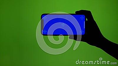 Girlish рука держит горизонтально умный телефон на зеленом экране сток-видео
