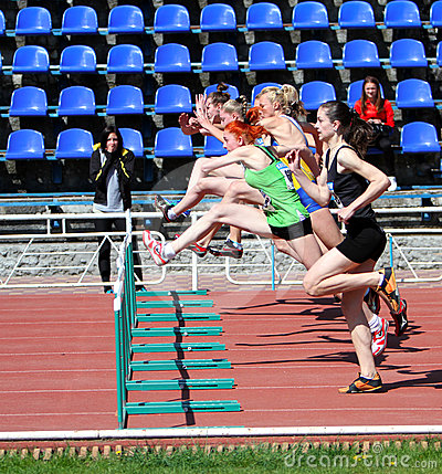 Girls on the 100 meters hurdles race Editorial Photo
